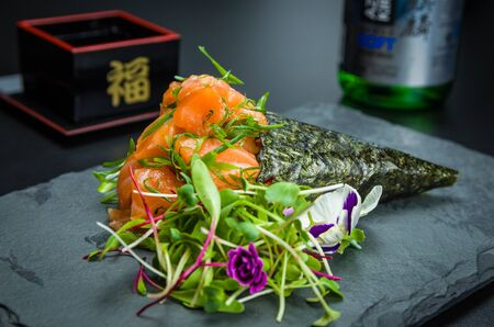 Sushi. Traditional Japanese cuisine, premium salmon Temaki decorated in an elegant setting.