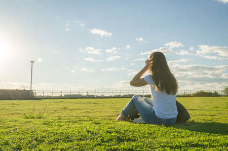 Young woman sitting on the grass with a protective mask during the SARS CoV-2 pandemic season , on the new Orla do Guaiba in Porto Alegre