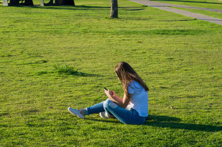 Young woman sitting on the grass with a protective mask during the SARS CoV-2 pandemic season  on the new Orla do Guaiba in Porto Alegre