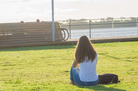Young woman sitting on the grass with a protective mask during the SARS CoV-2 pandemic season, on the new Orla do Guaiba in Porto Alegre
