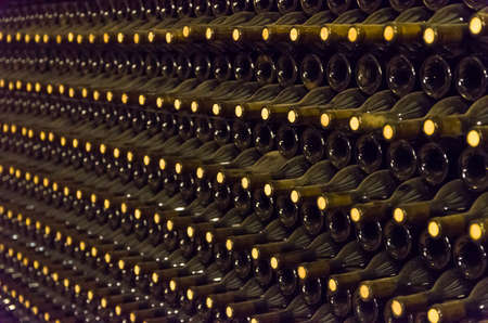 Wine bottles stored in the underground cellar for aging. Imagens