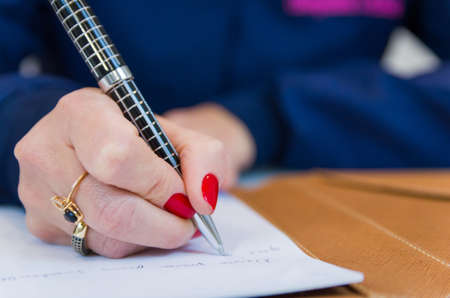 Close up of notepad and business woman writing