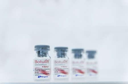 Porto Alegre, Brazil, April 10 - 2021: Botox glass medicine bottle, Syringe of botulinum toxin, hualuronic, collagen or flu on a white background