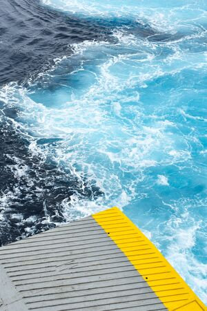 Greece, the view from the ferry as the ship sails into harbour. A close up detail of the loading ramp as it is lowered. The picture shows the contrast of blue and yellow, metal and sea.