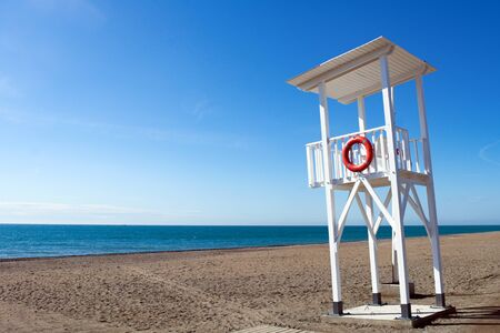 A bright sunny day at Torrox Costa, on the Costa del Sol, Spain. A view of the lifeguards station on the pristine beach. Clear blue sky - copy space.