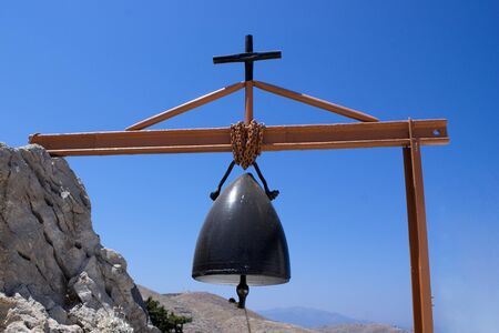 An improvised church bell made out of the cone of a war time artillery shell. Picture taken at the island of Symi in Greece.