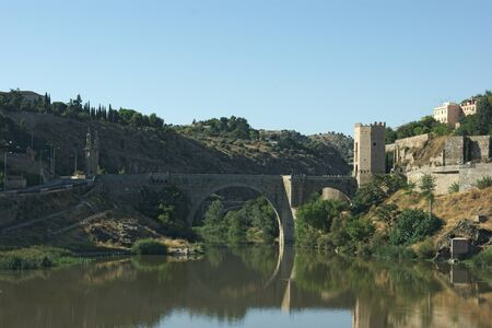 A view of the Alcantara bridge at Toledo, Spain. The elegant shape of the bridge is reflected on the still waters of the river Tagus.