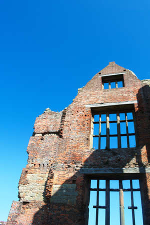 Vertical shot of the ruins of Moreton Corbet castle in Shropshire, England. Mullioned windows rise to the apex of a historic Tudor wall of an old castle - mansion. Blue skies - copy space.
