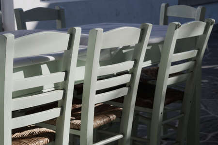 Folegandros island Greece. Greek taverna, close up shot with selective focus of typical, traditional restaurant furniture. No people, landscape aspect