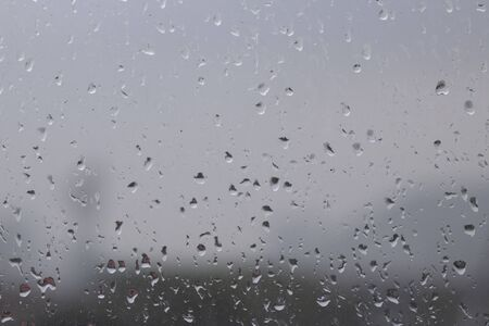 Rain on the surface of the window Stop and flow into the rain. With cloudy backgrounds, natural patterns of isolated raindrops
