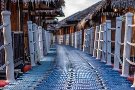 Long bridge, Wooden raft resort floating on Srinakarin dam in evening at kanchanaburi, Thailand. Blurred background.