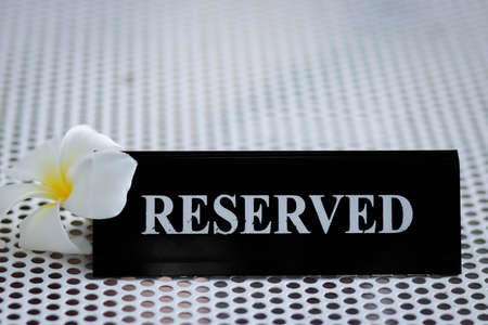 Reserved metal black plate in a restaurant. Reserved metal plate On the white table. vintage photo processing. close up of a setting a reserved sign on the restaurant table.