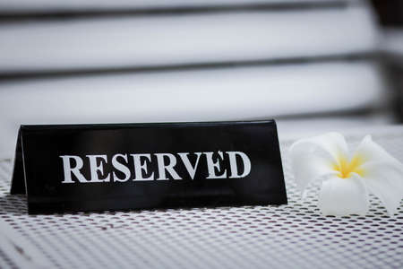 Reserved metal black plate in a restaurant. Reserved metal plate On the white table. vintage photo processing. close up of a setting a reserved sign on the restaurant table. Standard-Bild