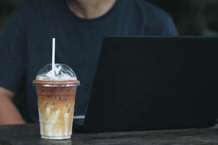 multitasking man using tablet, Laptop on wooden desk with iced coffee in the cafe. Stok Fotoğraf