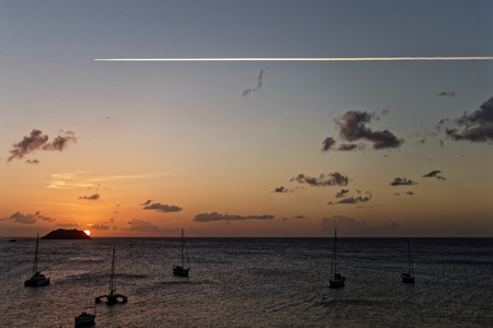 Plane in the sky over the sunset in anse Mitan, Les Trois-Ilets, Martinique FWI