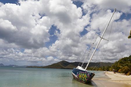 Sainte-Anne, Martinique, FWI - Graffiti on an abandoned beached sailboat in Pointe Marin beach
