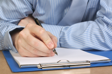 fountain pen writing: Cropped image of a businessman in shirt and tie writing notes on a clipboard with a fountain pen Stock Photo