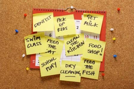 家事のリマインダーとして黄色の付箋紙のノートで覆われているコルク掲示板に壁掛けカレンダー