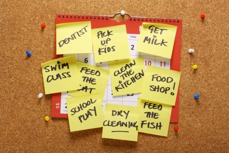 tasks: A wall calendar on a cork notice board covered with yellow sticky paper notes as a reminder of household chores