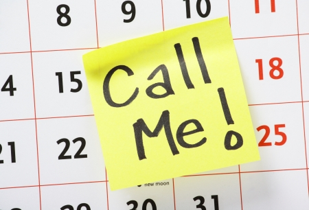 Call Me with an exclamation mark written by hand on a yellow sticky paper note and stuck to a wall calendar photo