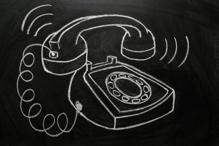 landline: Telephone ringing off the hook drawn on a blackboard as a communication concept