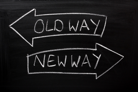 Old Way, New Way written on a blackboard with arrows pointing in the right direction Stock Photo