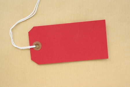 Red paper luggage tag or label with copy space on a brown wrapping paper Stock fotó