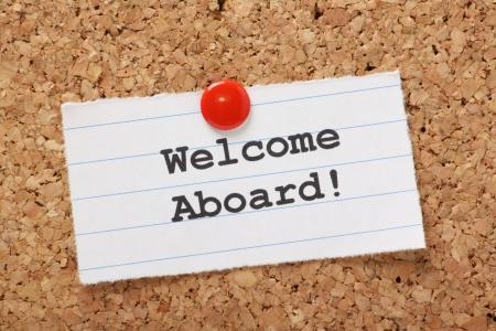 phrases: La frase Bienvenido a bordo escrito en un trozo de papel rayado y clavado en un tabl�n de corcho