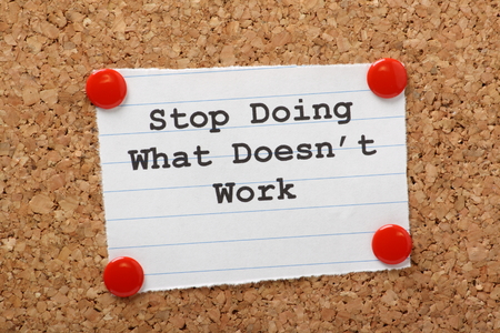 The phrase Stop Doing What Doesn t Work on a paper note pinned to a cork notice board