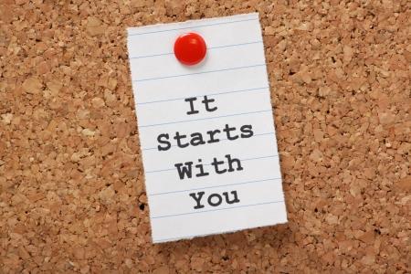 Die Worte, es beginnt mit Ihnen auf ein Stück Papier liniert eingegeben und mit einem Korken Schwarzes Brett Standard-Bild