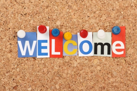 The word Welcome in cut out magazine letters pinned to a cork notice board Stock Photo