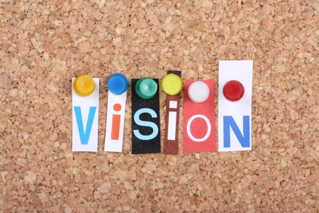 board pin: The word Vision in cut out magazine letters pinned to a cork notice board Stock Photo