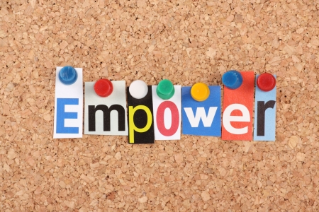 The word Empower in cut out magazine letters pinned to a cork notice board Stock Photo