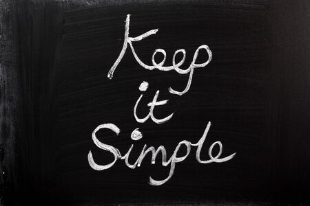 Keep It Simple written in chalk on a used blackboard  A well known saying for business strategy, project management and planning