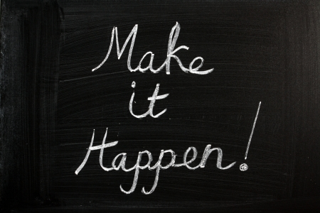 Make It Happen written in chalk on a used blackboard  Used in business, life and sports coaching this well known phrase or saying has become a rallying cry for getting things done