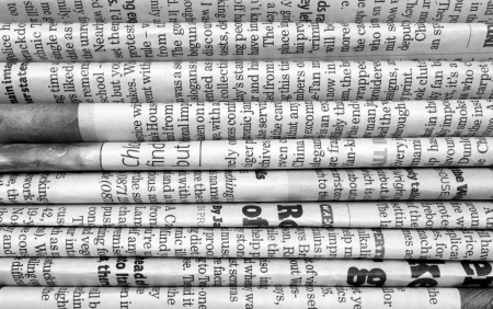 current events: A black and white background of English language newspapers stacked and folded in a horizontal position and viewed in close up