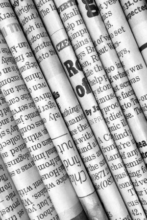 A black and white background of English language newspapers folded and stacked in a diagonal position and viewed in close up photo