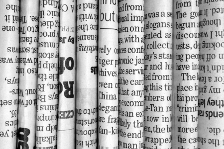 A black and white background of English language newspapers stacked and folded in a vertical position and viewed in close up