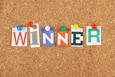 first place: The word Winner in cut out magazine letters pinned to a cork notice board  We look for winners in competitive sports, competition and business  Stock Photo