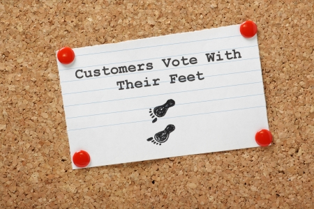 Customers Vote With Their Feet typed on a paper note pinned to a cork notice board  photo