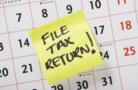 Hand schriftlicher Mahnung auf einem gelben Post-It auf einem Kalender-Hintergrund stecken Hinweis Dateisteuererklärung Standard-Bild - 24747011