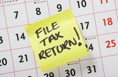 Hand written reminder to File Tax Return on a yellow post it note stuck to a calendar background Stock Photo