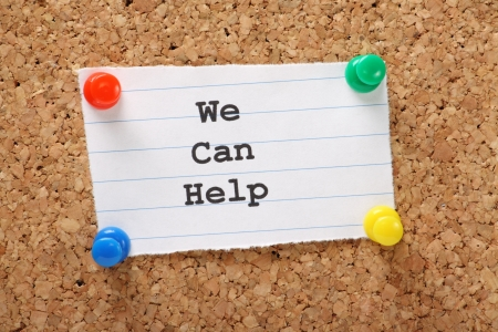 can we help: Paper note pinned to a cork notice board with the phrase We Can Help typed onto it