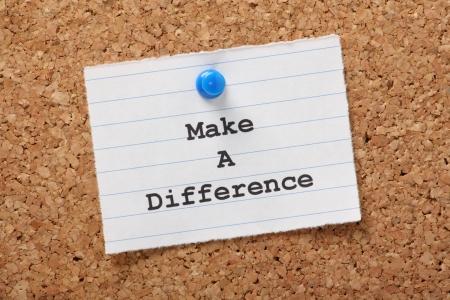De uitdrukking Make A Difference op een papieren notitie gespeld aan een kurk prikbord