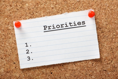 priorities: A blank list of Priorities on a paper note pinned to a cork notice board  In business and in life we draw up lists of actions to aid us in getting things done