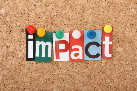 tangible: The word Impact in cut out magazine letters pinned to a cork notice board Stock Photo