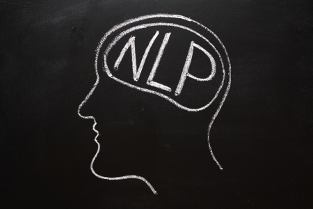 Drawing on a blackboard of a human head in profile with NLP on the brain  NLP is the acronym for Neuro-Linguistics Programming, often used in business and Psychotherapy for self improvement