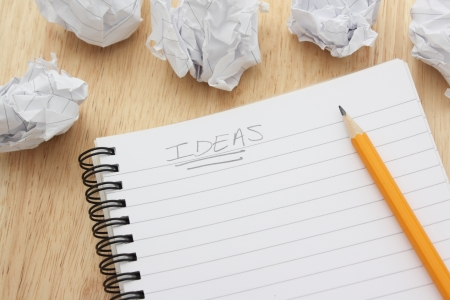 Ideas written on a blank notepad and surrounded by waste paper photo