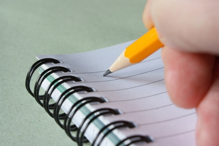 Close up of a hand writing notes with a yellow pencil on a spiral notebook with lined paper