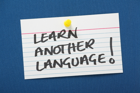 A reminder to learn another language written on a white note card and pinned to a blue notice board  A second language benefits our job prospects and helps business trade in a competitive market